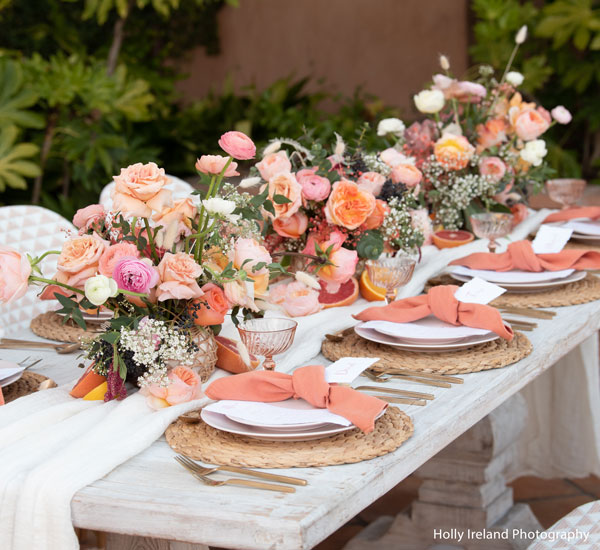 Rancho Valencia table setting with flowers down the center, napkins, menus and place cards on each table setting