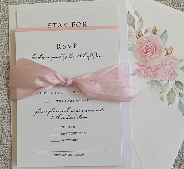 wedding invitation suite in white and blush with black text