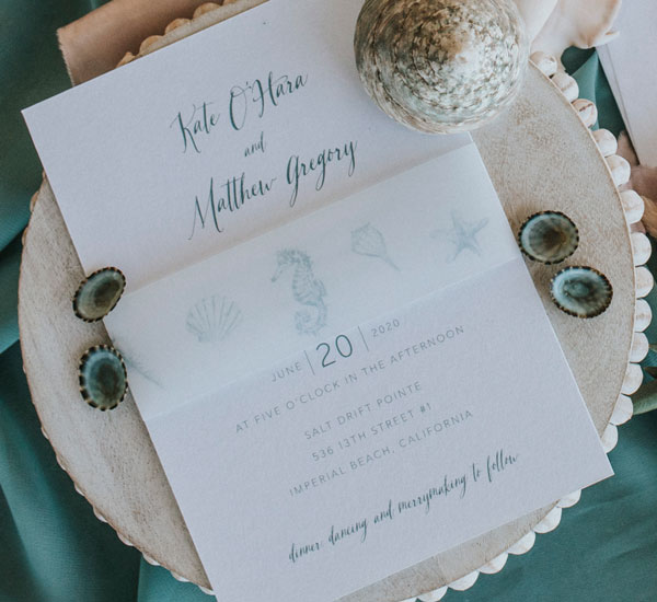 Invitation with beach theme belly band printed with shells and seahorse