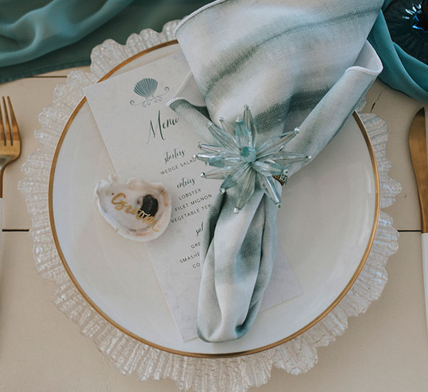 Menu with shell design at top in beach theme place setting