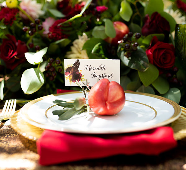 place card in holder on plate in table setting with nectarine decoration